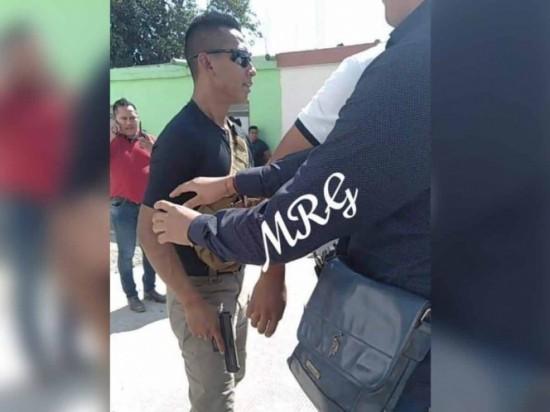 Por protesta campesina, policía saca su arma en gira de López Obrador.